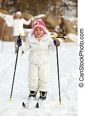 Child skiing - Happy girl in winterwear skiing with her...