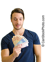 Successful young man looking at euro banknotes - Successful...