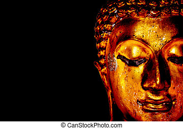 Old golden Buddha statue on a black background.