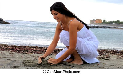 woman playing with sand on beach