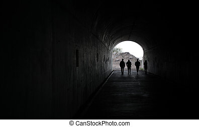 Men in the dark tunnel - Silhouette of 4 persons walking...
