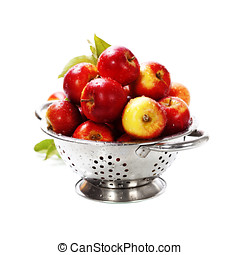 Fresh red apples in metal colander over white