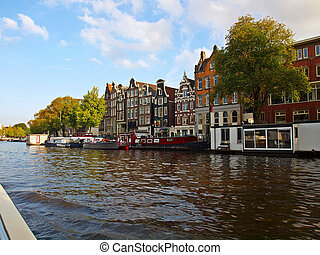Amsterdam canals and typical houses with clear summer sky.