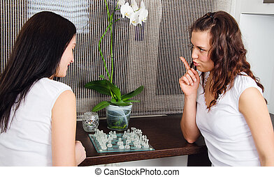 Two young beautiful women play chess at home
