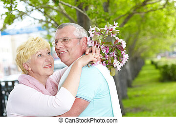 Husband and wife - Happy mature woman with blooming bouquet...