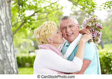 Romance - Happy mature woman with blooming bouquet kissing...