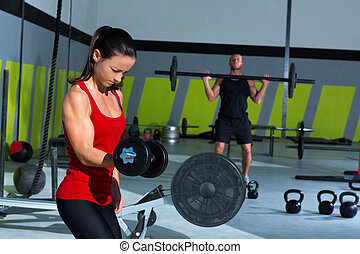 girl dumbbell and man weight lifting bar workout at Cross...