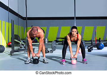 Kettlebells swing Cross fit exercise man and woman workout...