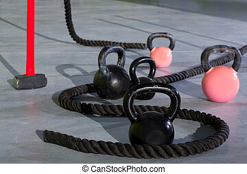Cross fit Kettlebells ropes and hammer in fitness gym floor