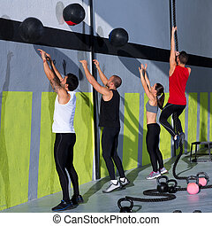 Cross fit workout people group with wall balls and rope at...
