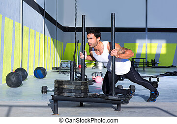 Cross fit sled push man pushing weights workout exercise