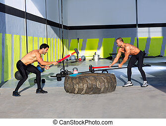 Cross fit sledge hammer men workout at gym