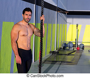 Cross fit man with climbing rope relaxed at gym
