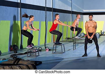 Cross fit box jump people group and kettlebell man at gym