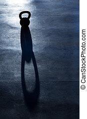 Cross fit Kettlebell weight backlight and shadow on the gym...