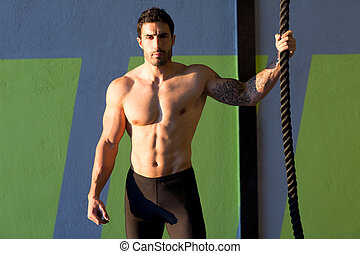 Cross fit gym man holding hand a climbing rope - Cross fit...