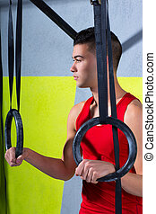 Cross fit dip ring young man relaxed after workout