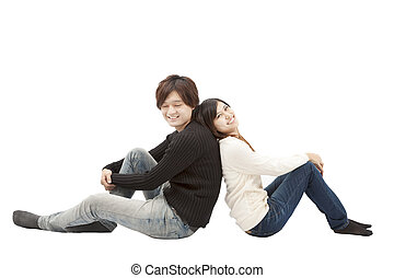 young asian couple sitting together and isolated on white