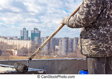 Creating waterproofing barrier - Roofer worker painting...