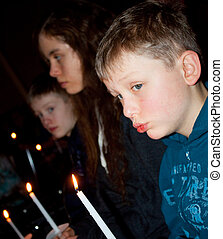 Children at Candle light service - three children holding...