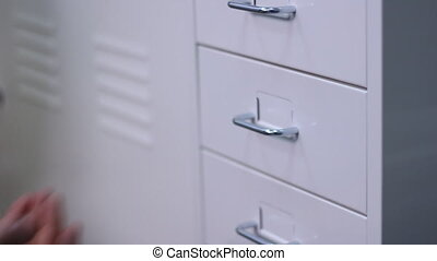 Man opening a drawer in a cabinet