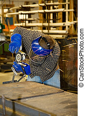 Welder Grinding Metal - Welder using a grinder to smooth a...