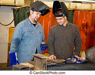 Welders Discussing the Job - Two welders in a factory...