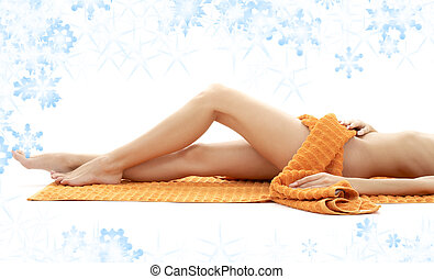 long legs of relaxed lady with orange towel and snowflakes