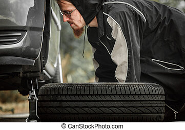 Young adult inspecting the wheel of a car