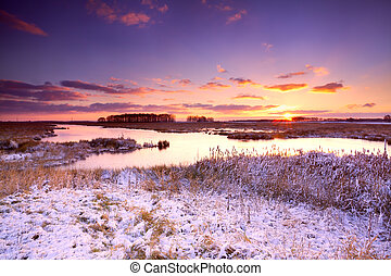 dramatic sunrise over frozen lake in winter