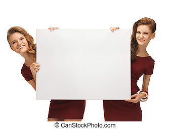 two teenage girls in red dresses with blank board - picture...