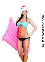 Young woman in bikini and christmas hat holding inflatable mattress. Isolated on white
