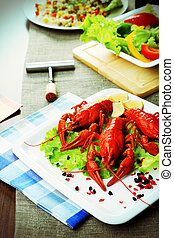 Dinner table dished up with boiled crawfish and vegetable...