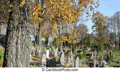 people cemetery autumn - people walk in rural cemetery and...
