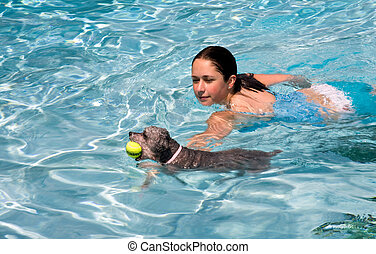 Girl swimming with dog - Teenage girl swimming in pool with...