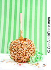 caramel candy apple with peanuts on a stick with green...