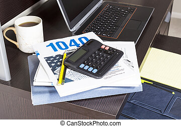 Income Tax Season - Pile of tax returns with computer, cup...