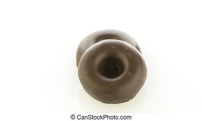 Chocolate donut cookies rotating on white background.