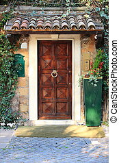 Renaissance front door with roofing and plants