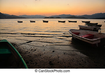 Sunset at Beach - Sunset at beach with boat in the water. In...