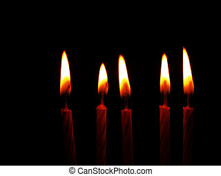 Five red candles burning in the dark - black background