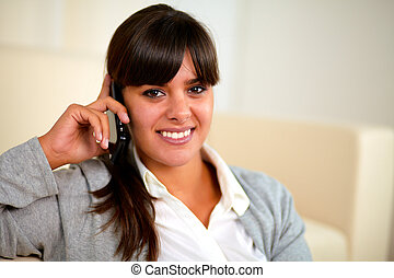 Smiling young woman speaking on cellphone