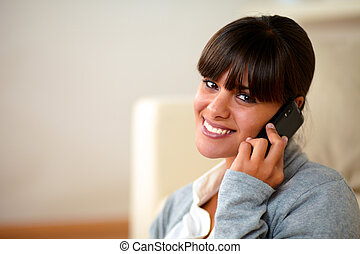 Attractive young female conversing on mobile phone -...