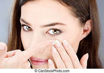 woman putting contact lens - Close up of a woman putting...