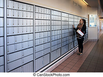 Post office mail boxes lining a wall outside