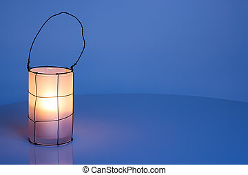 Cozy lantern on blue winter background, with copy space
