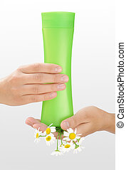 Hands of young woman holding cosmetics bottle and fresh chamomile