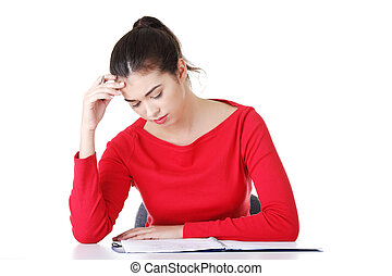 Pretty young woman in casual clothes sitting at the desk -...