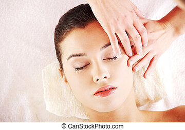 Beautiful young relaxed woman enjoy receiving face massage...