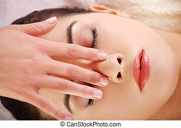 Woman enjoy receiving face massage at spa saloon
